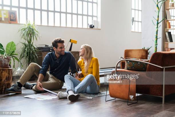 smiling businessman and businesswoman sitting on the floor discussing documents in loft office - sitting on ground stock pictures, royalty-free photos & images