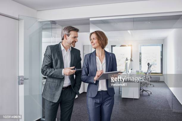 smiling businessman and businesswoman using tablet in office together - cara a cara imagens e fotografias de stock
