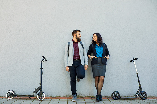 Smiling businessman and businesswoman with scooters leaning against a wall - gettyimageskorea