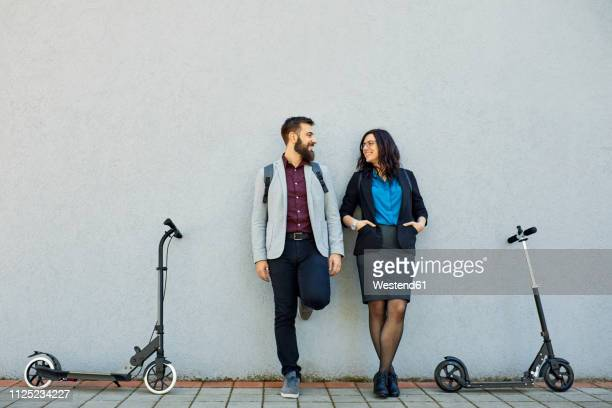 smiling businessman and businesswoman with scooters leaning against a wall - 30代の男性 ストックフォトと画像