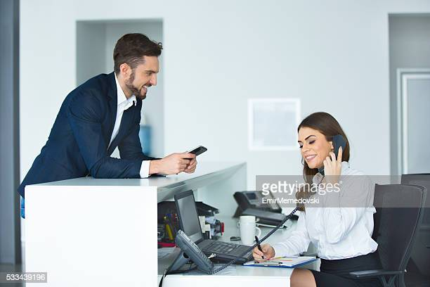 Smiling businessman and female receptionist at the secretary desk.