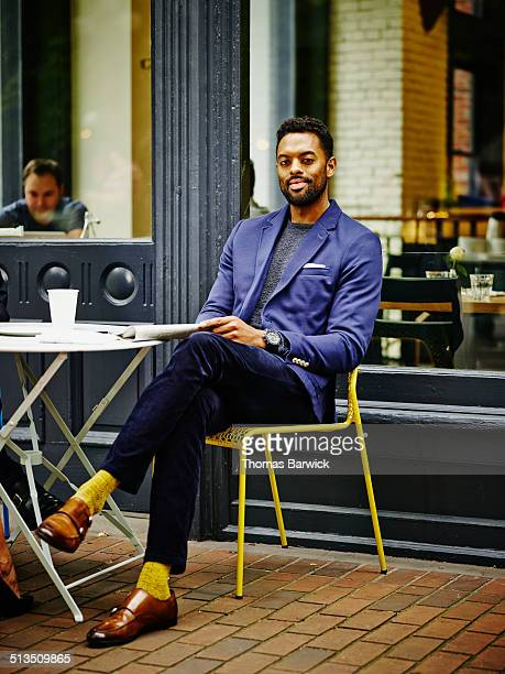 smiling businessman at outdoor table of urban cafe - 足を組む ストックフォトと画像