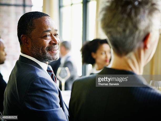 Smiling businessman at table during lunch meeting