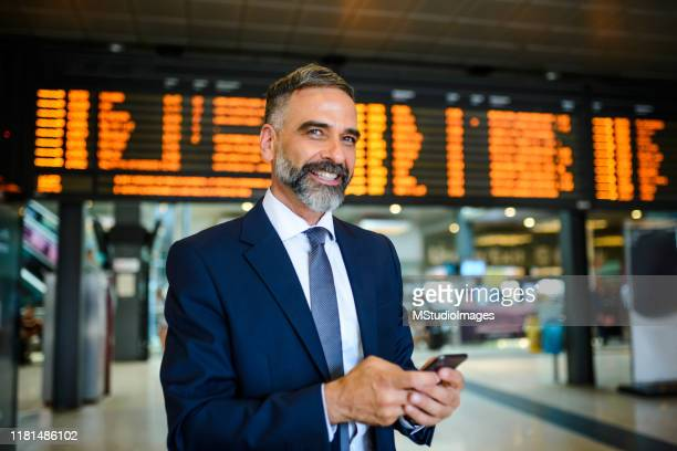 uomo d'affari sorridente in aeroporto che controlla il volo - stazione della metropolitana foto e immagini stock