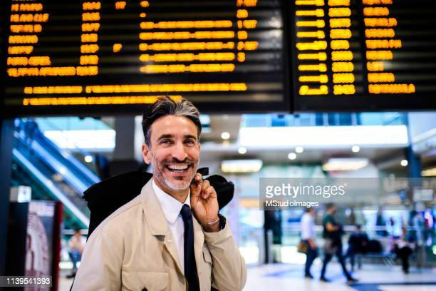 smiling businessman at the train station. - information sign stock pictures, royalty-free photos & images
