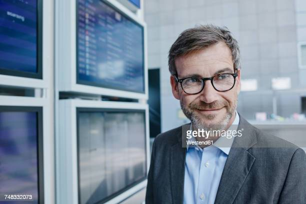 Smiling businessman at timetable at the airport