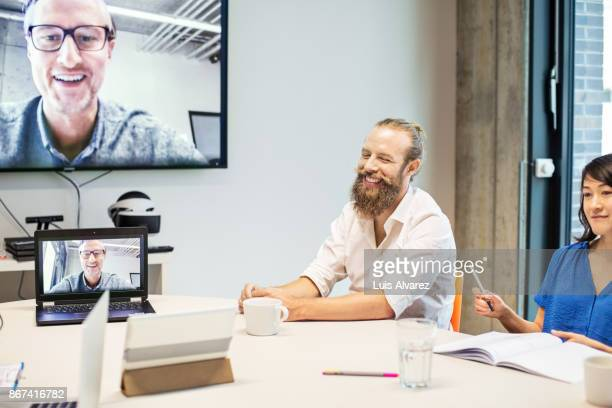 Smiling businessman attending video conference in board room