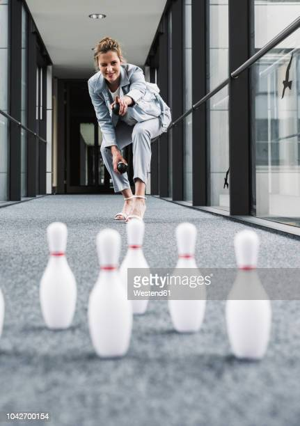 smiling businessman bowling in office passageway - drive ball sports stock pictures, royalty-free photos & images
