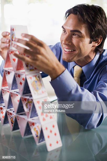 Smiling businessman building house of cards