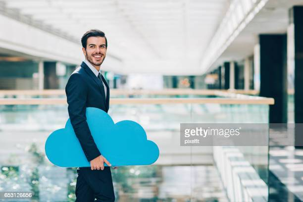 Smiling businessman carrying a big blue cloud