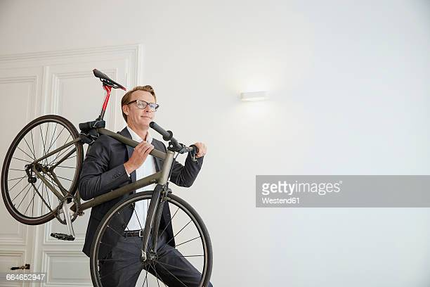 Smiling businessman carrying racing cycle on his shoulder