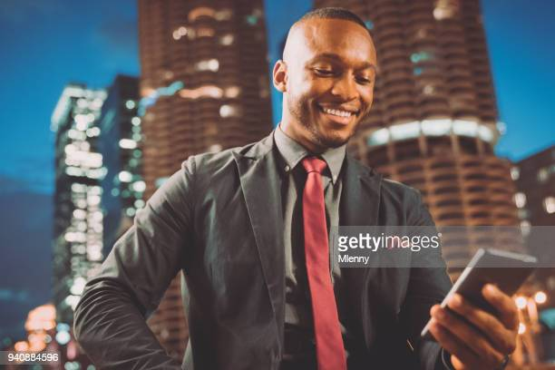 Smiling businessman checking messages on mobile phone in chicago