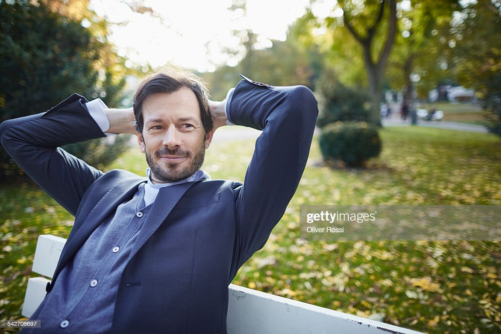 Smiling businessman contemplating on bench in park : Stock Photo