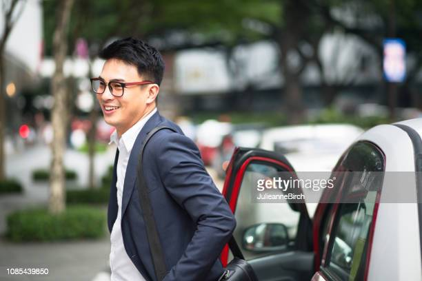smiling businessman disembarking from cab - disembarking stock pictures, royalty-free photos & images