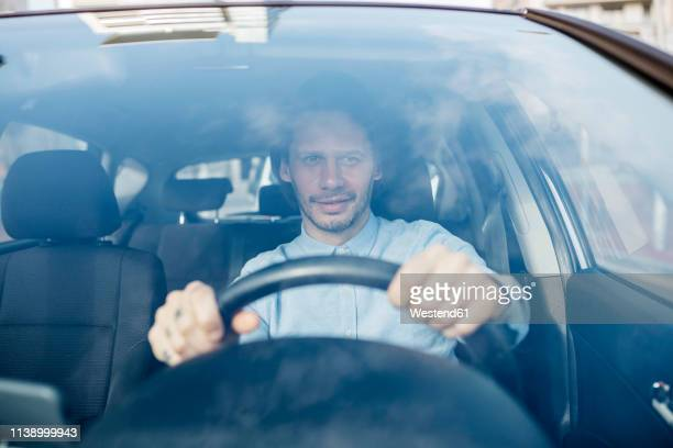 smiling businessman driving car - frontaal stockfoto's en -beelden