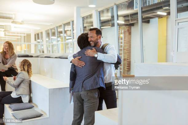 smiling businessman embracing male colleague while standing in office - arm around stock pictures, royalty-free photos & images
