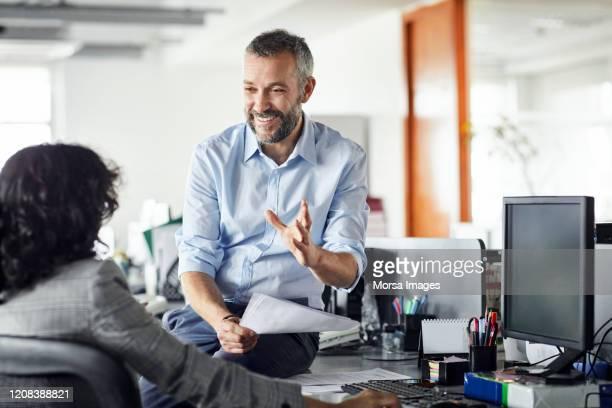 lächelnder geschäftsmann erklärt strategie im büro - 50 54 jahre stock-fotos und bilder