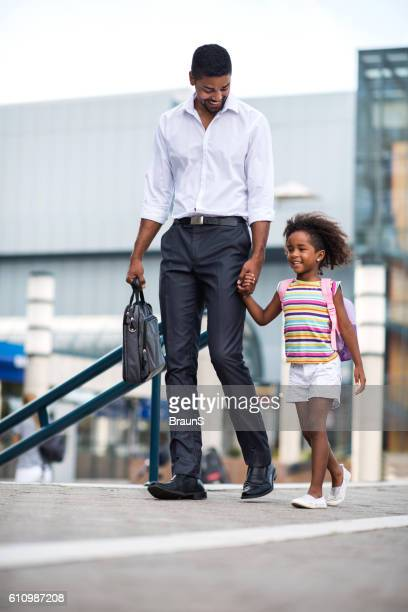 Smiling businessman father taking his daughter to school.