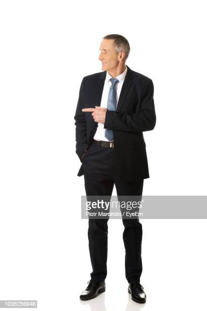 smiling businessman gesturing against white background - hands in pockets stock pictures, royalty-free photos & images