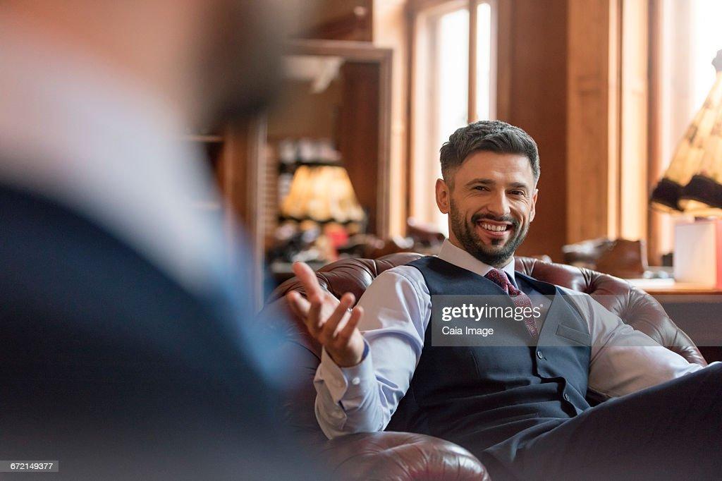 Smiling businessman gesturing in menswear shop : Stock Photo