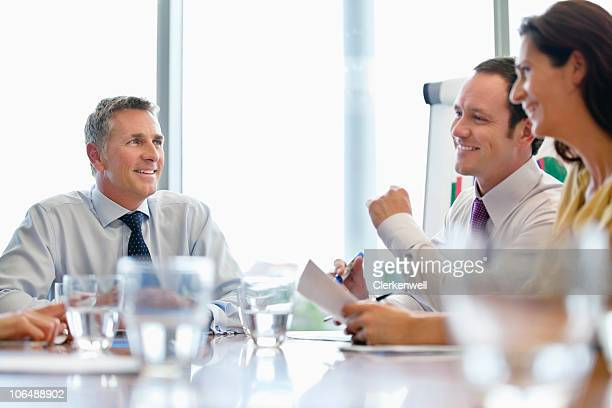 Smiling businessman giving presentation to co workers at conference room