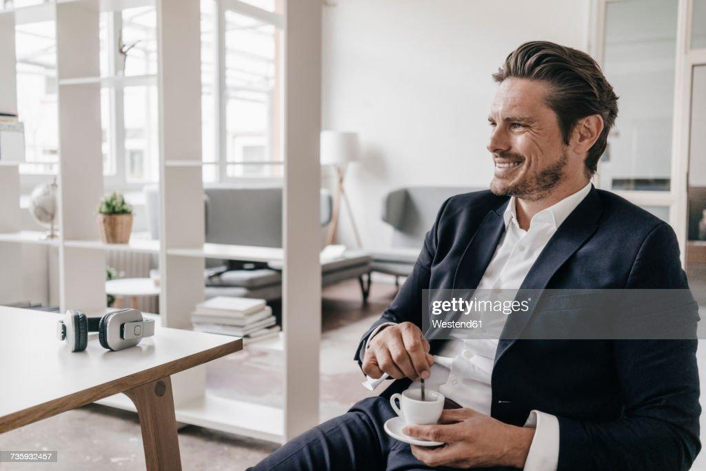 Smiling businessman having a coffee break : Stock Photo