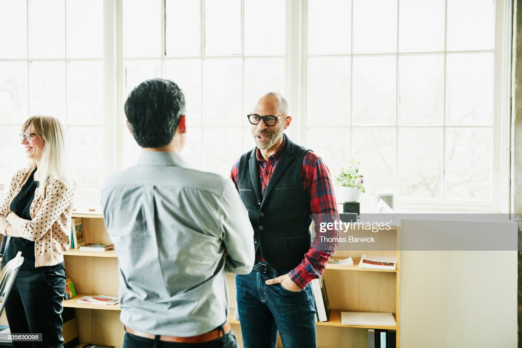 Smiling businessman having informal project meeting with coworker in design office : Stock Photo