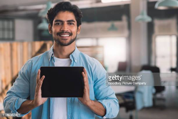 smiling businessman holding a digital tablet with a blank screen - holding aloft stock pictures, royalty-free photos & images