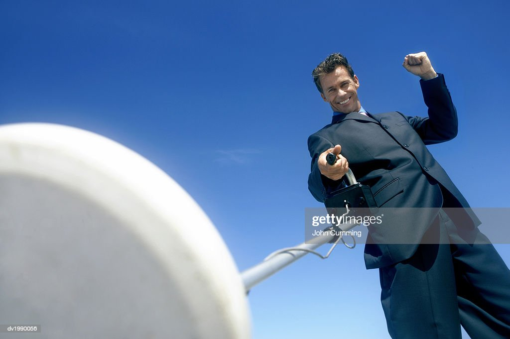 Smiling Businessman Holding a Satellite Dish : Stock Photo