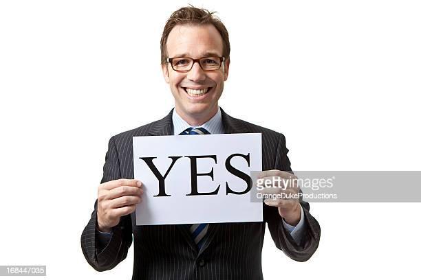 Empresario sonriente sosteniendo un cartel