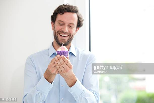 Smiling businessman holding birthday cupcake