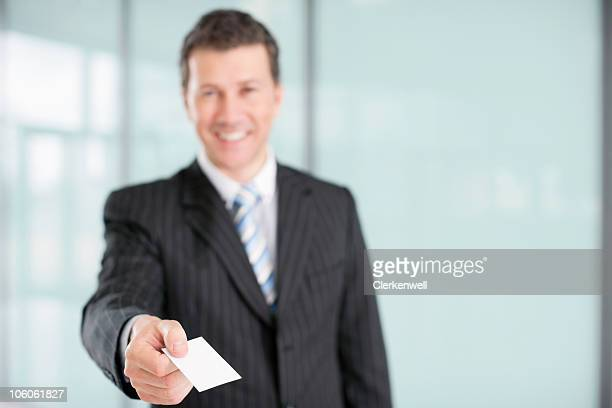 Smiling businessman holding blank business card