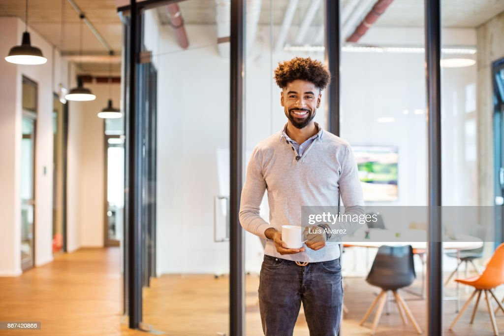 Smiling businessman holding coffee cup in front of board room : Stock Photo