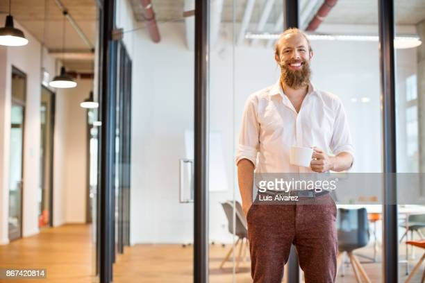 smiling businessman holding coffee cup in office - hipster person stock-fotos und bilder