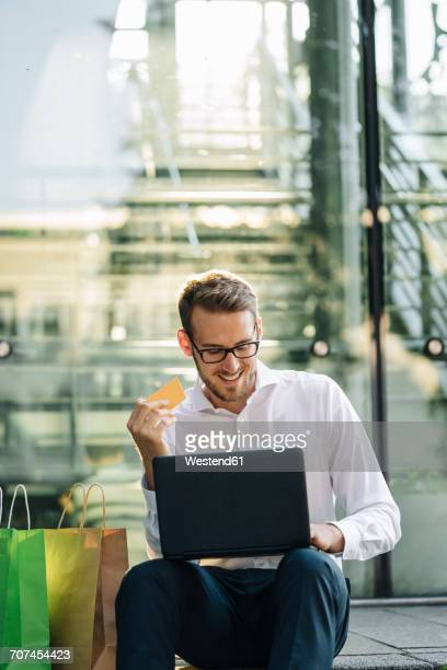 Smiling businessman holding credit card and using laptop next to paper bags