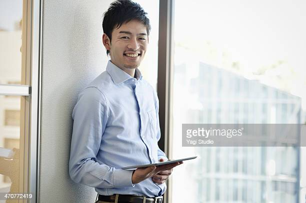 smiling businessman holding digital tablet - 25 29歳 ストックフォトと画像