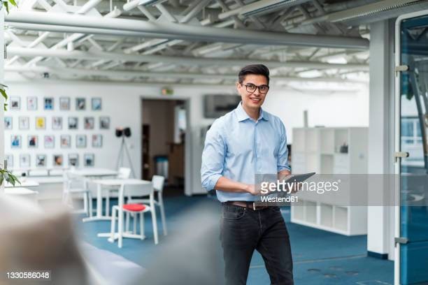 smiling businessman holding digital tablet while walking in office - three quarter length stock pictures, royalty-free photos & images