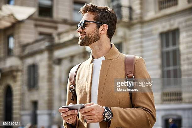 smiling businessman holding phone and looking away - watch timepiece stock pictures, royalty-free photos & images