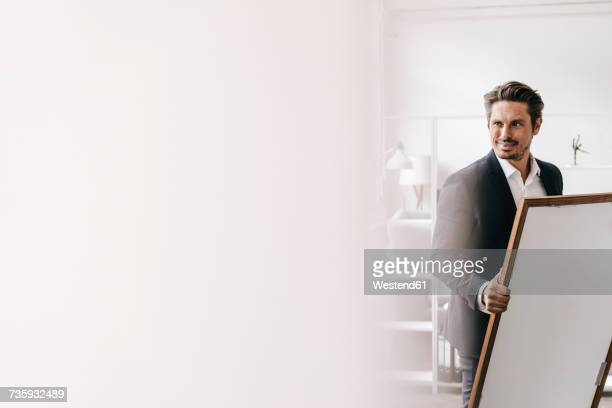 smiling businessman holding picture frame - art dealer stock pictures, royalty-free photos & images