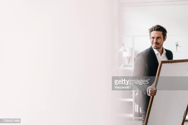 smiling businessman holding picture frame - kunsthändler stock-fotos und bilder