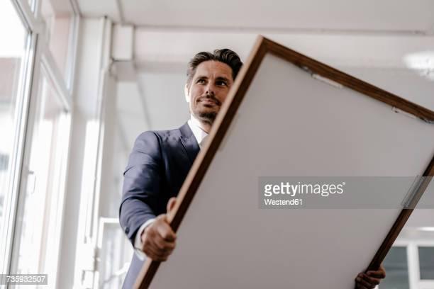 Smiling businessman holding picture frame