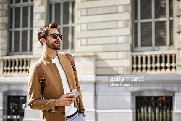 Smiling businessman holding smart phone in city