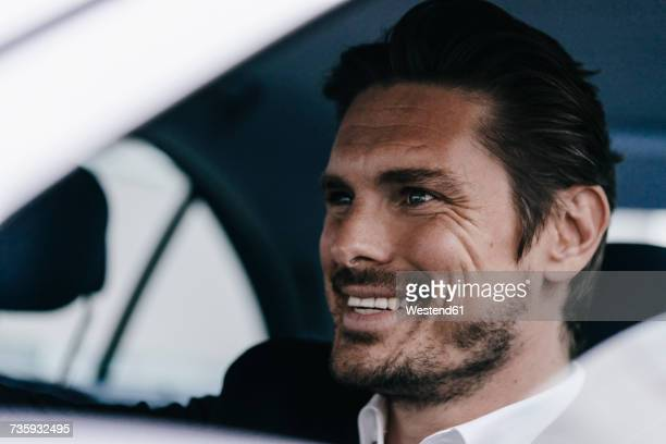 smiling businessman in a car - genot stockfoto's en -beelden