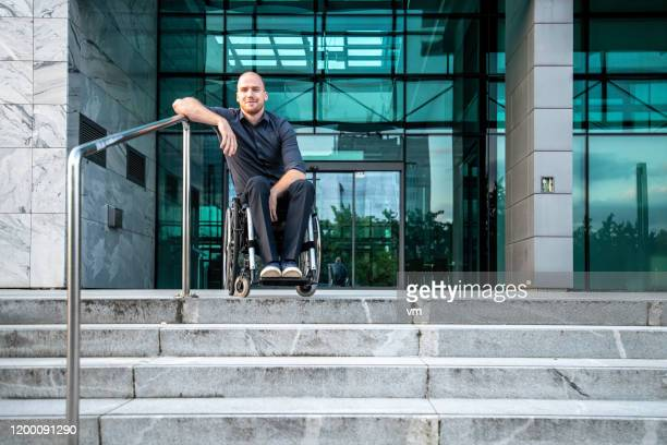 smiling businessman in a wheelchair leaning on staircase railing - leaning stock pictures, royalty-free photos & images