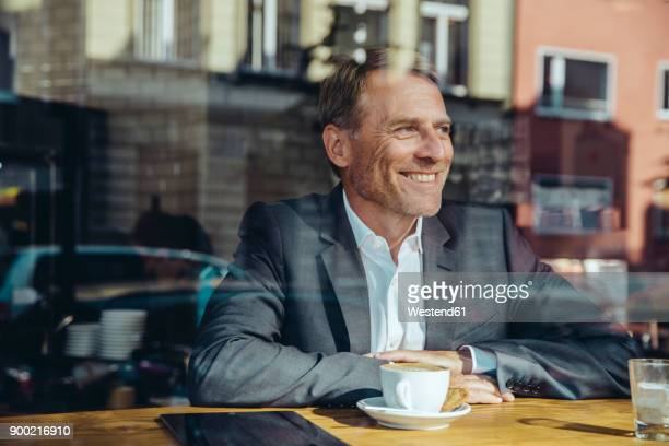 smiling businessman in cafe looking out of window - positive emotionen stock-fotos und bilder