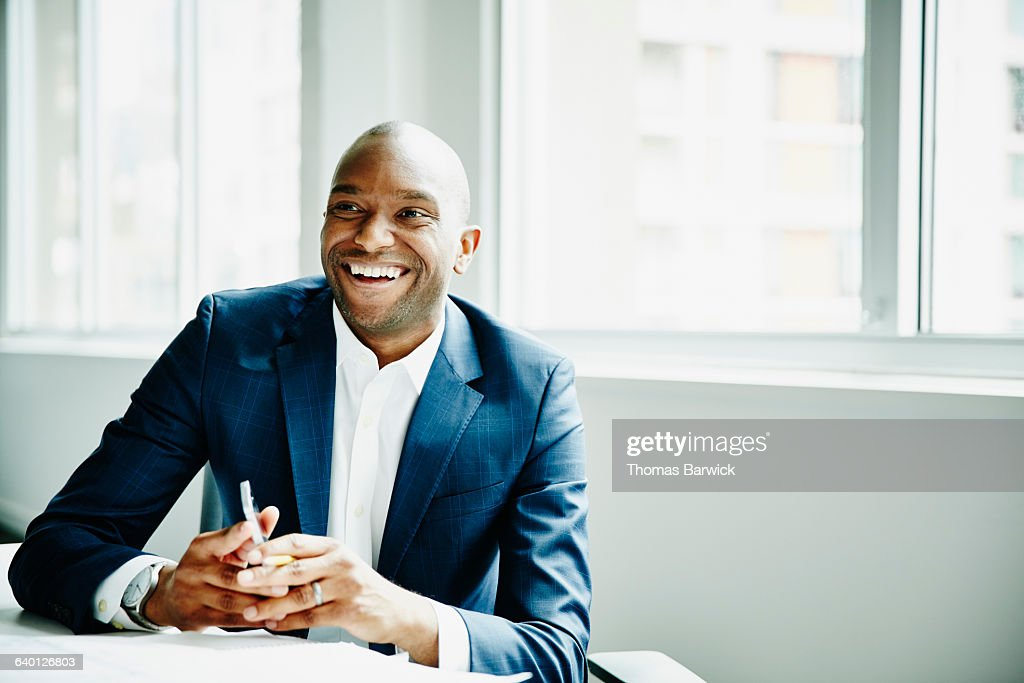 Smiling businessman in discussion at workstation : Stock-Foto