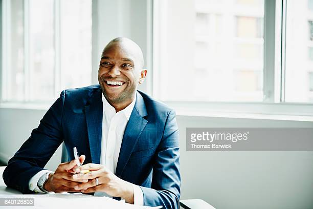 smiling businessman in discussion at workstation - wegkijken stockfoto's en -beelden