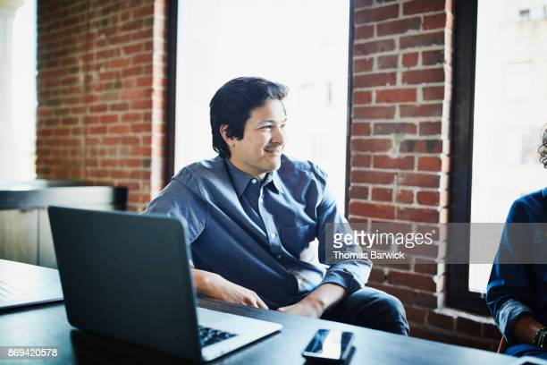 Smiling businessman in discussion with client in office conference room