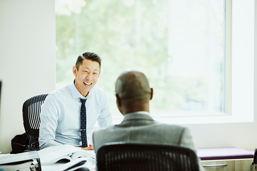 Smiling businessman in discussion with client in office - gettyimageskorea