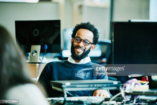 smiling businessman in discussion with colleague in high tech startup office - white collar worker stock pictures, royalty-free photos & images